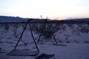 Old rusty swing set in the desert sunset